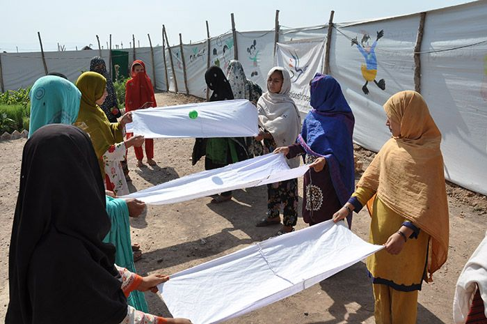 Pakistan, young girls playing a game where they roll a ball on stretched strips of white fabric