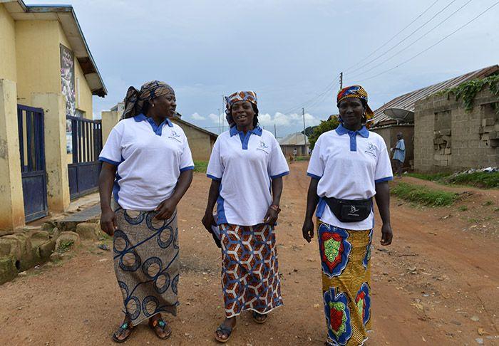 Three NIgerian women walking down a village street in Nigeria