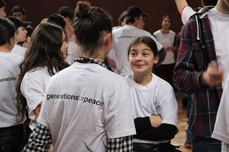 Young teenagers wearing Generations For Peace t-shirts talking and smiling