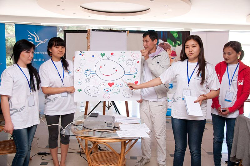 Kyrgyzstan, volunteers gathered around their artwork representing smiley faces