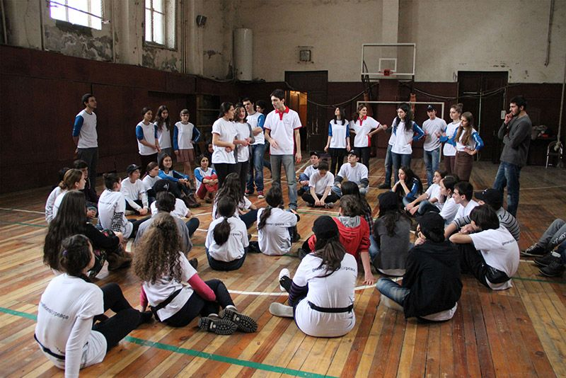 Volunteers talking to children in a gymnasium, all wearing Generations For Peace t-shirts