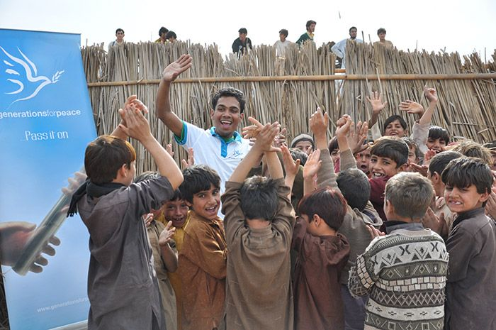 Pakistan, young boys cheering with a Generations For Peace volunteer