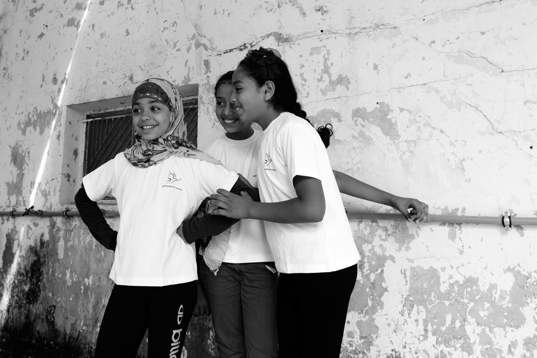young girls smiling wearing Generations for Peace t-shirts